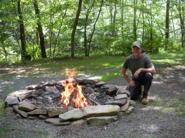 man kneeling next to a blazing campfire pit