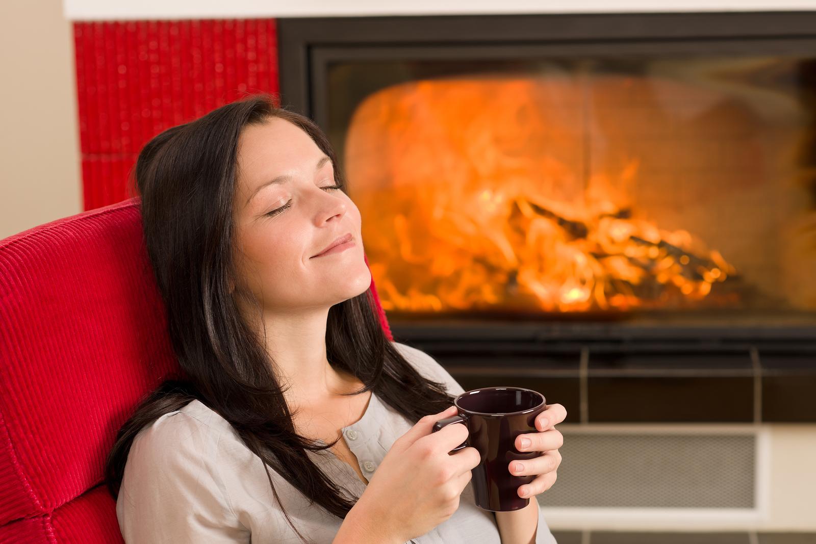 girl enjoying cup of coffee next to woodstove