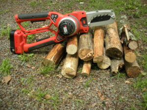 alligator chain saw tool on top of wood logs