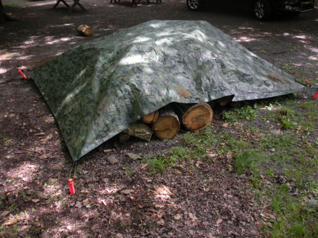 large camo tarp stretched over a wood pile by bugee cords and orange ground stakes