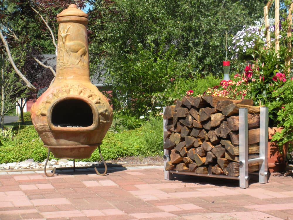 firewood holder filled with split wood on patio next to a chimenea