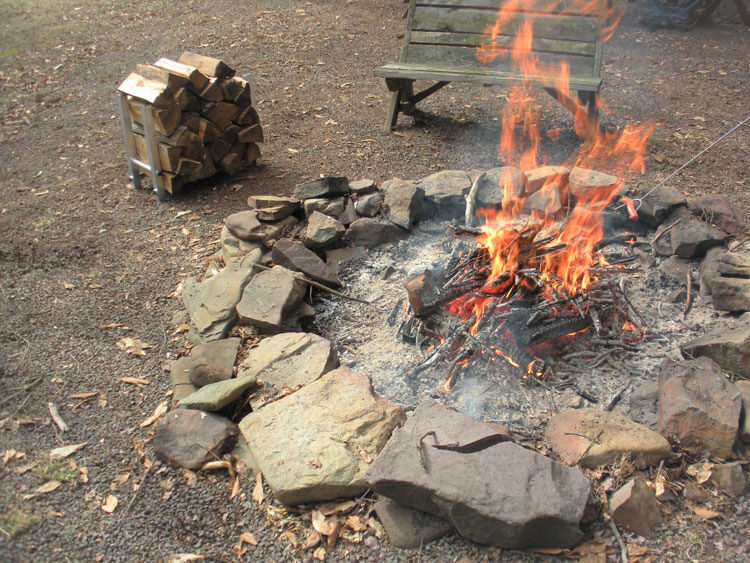 TFH-1 aluminum firewood holder filled with firewood next to outdoor firepit with campfire